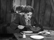 Charlie Chaplin carving up a boot in The Gold Rush